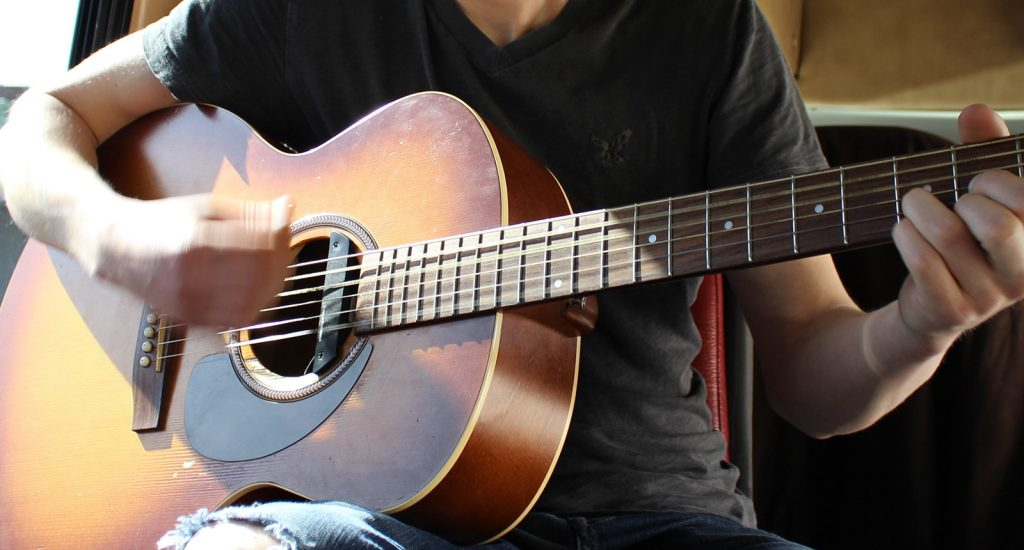 Musician strumming on guitar
